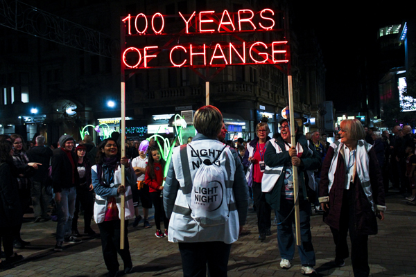 A group of light night volunteers holding up a neon sign that reads 100 Years of Change